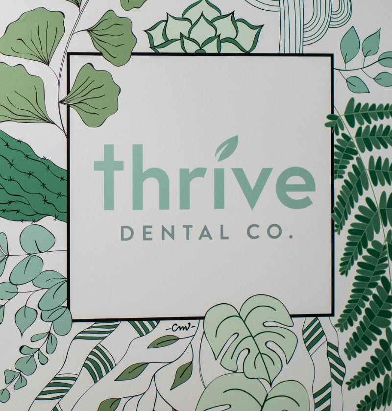 Photo of a leafy wall mural displaying the Thrive Dental Co. logo