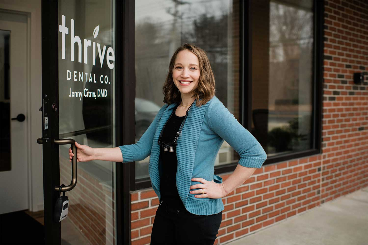 Photo of Acton, MA dentist Jenny Citrin, standing outside the front door of her dental practice