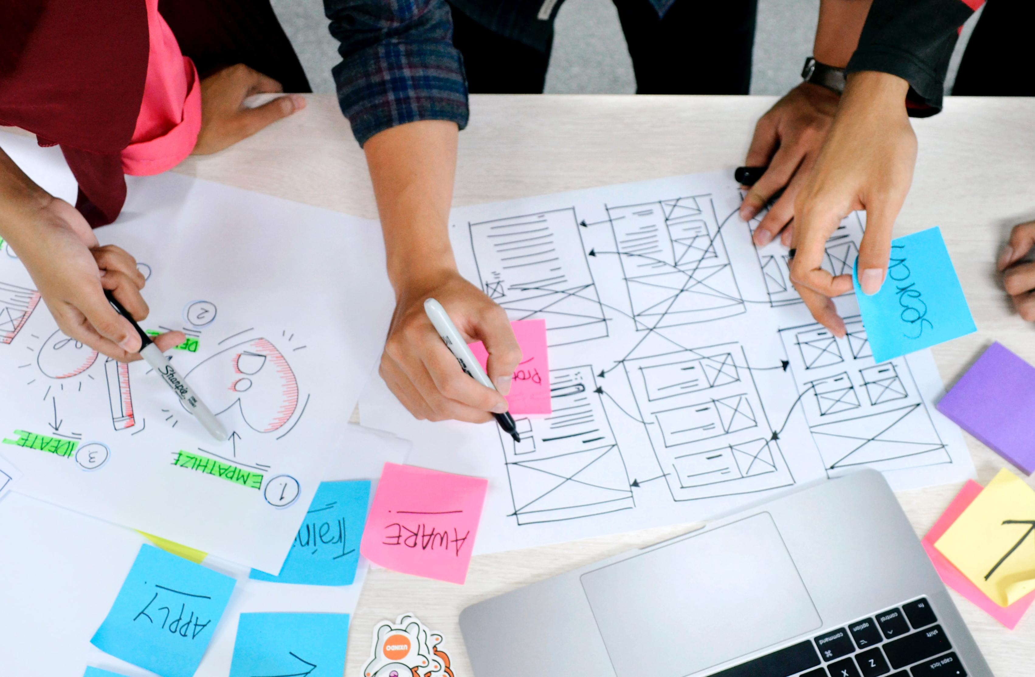 Symbolbild für eine fachliche Diskussion. Tisch mit Papier und Postits. Hände halten Stifte darüber.