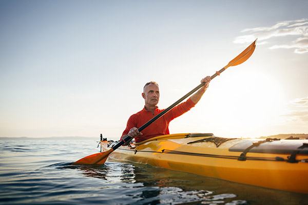 A man kayaking in open water
