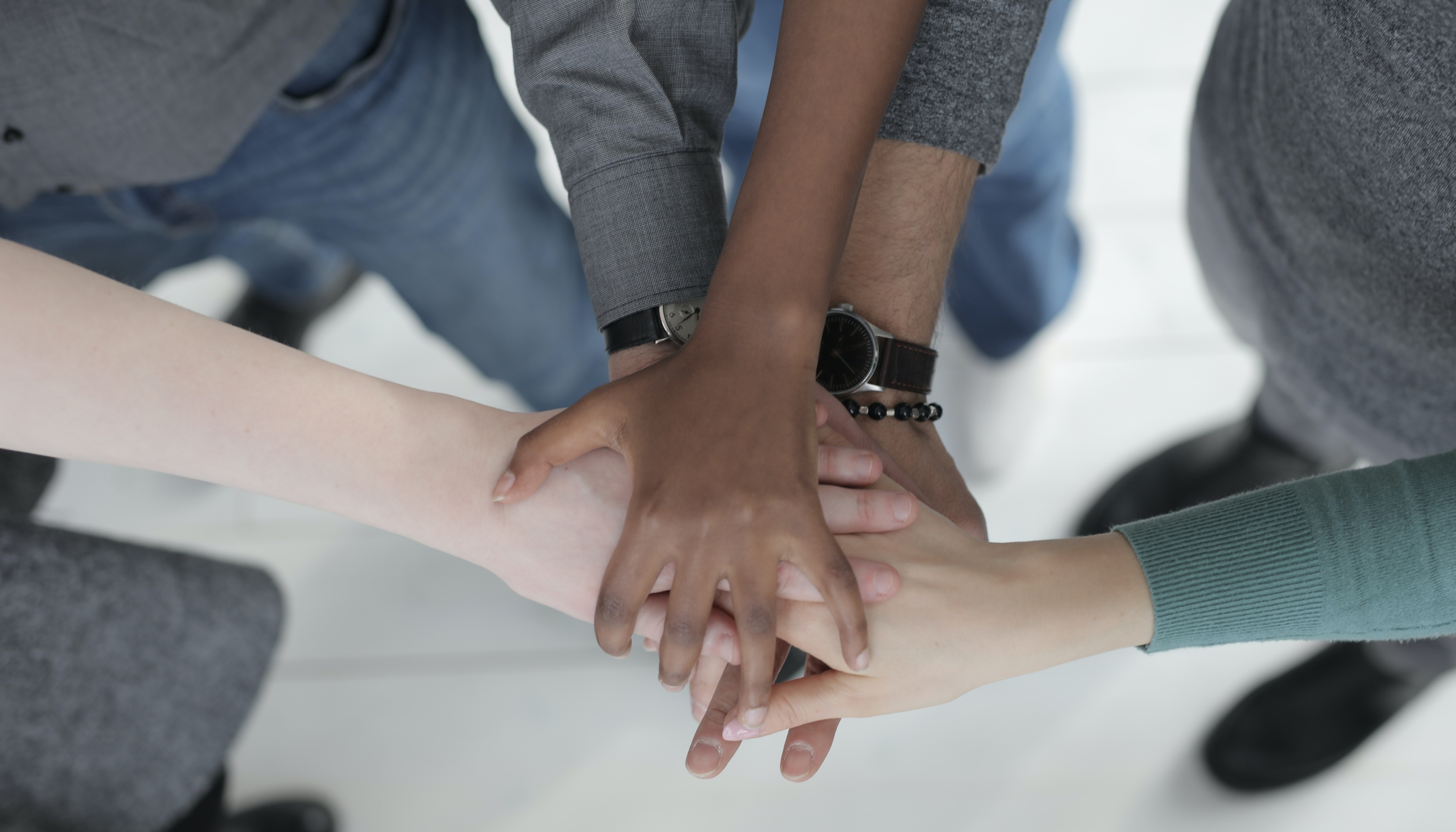 Multiethnic colleagues joining hands | Photo by Andrea Piacquadio from Pexels