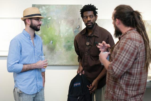 Three men discuss artwork at an InSpero event