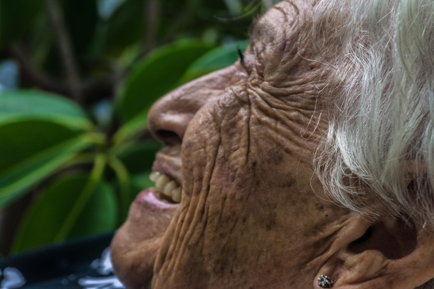 old wrinkly lady smiling and looking up green plants background