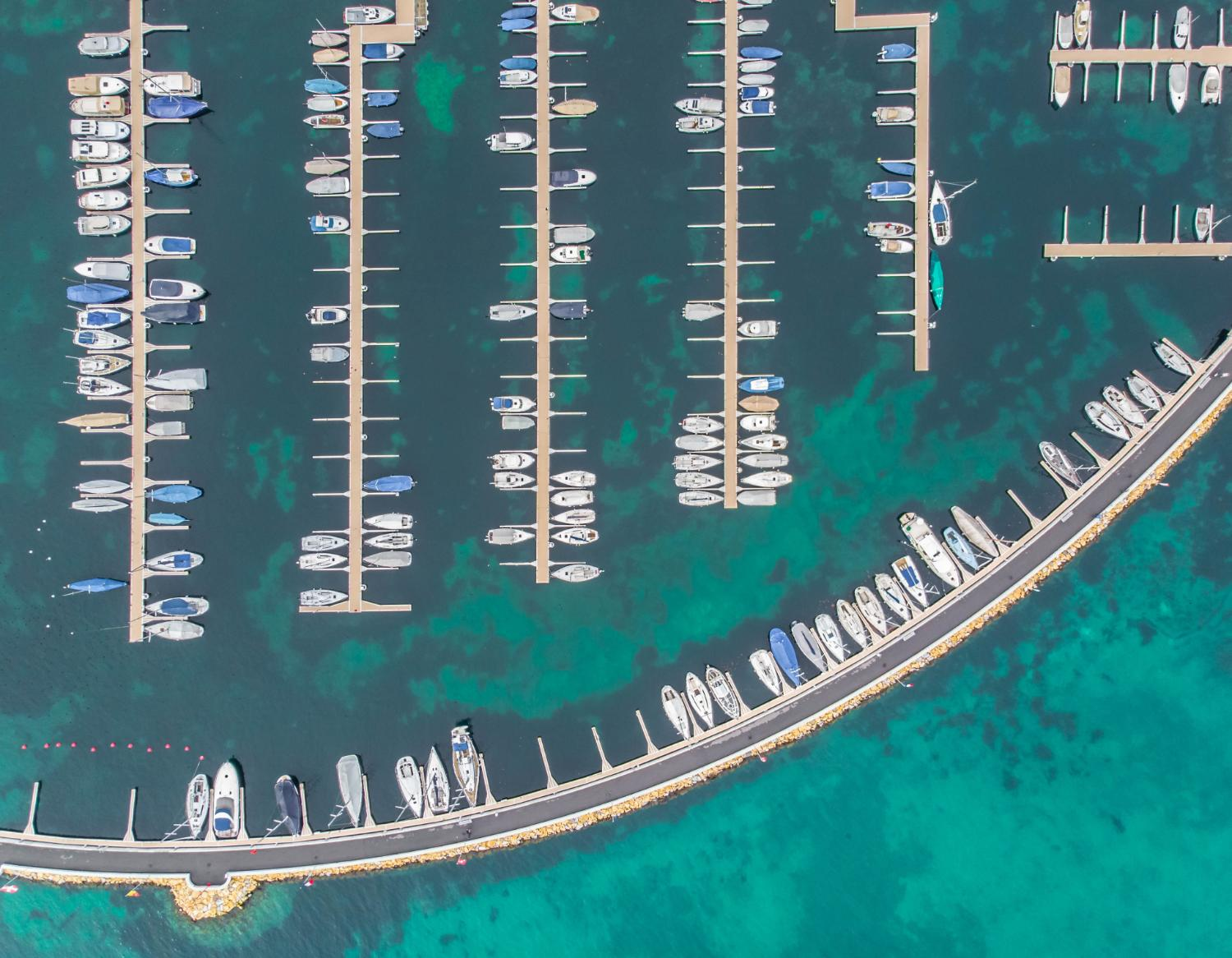 man made curved marina with boats from the sky birds eye drone
