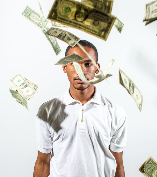 A black man standing with money falling from the sky