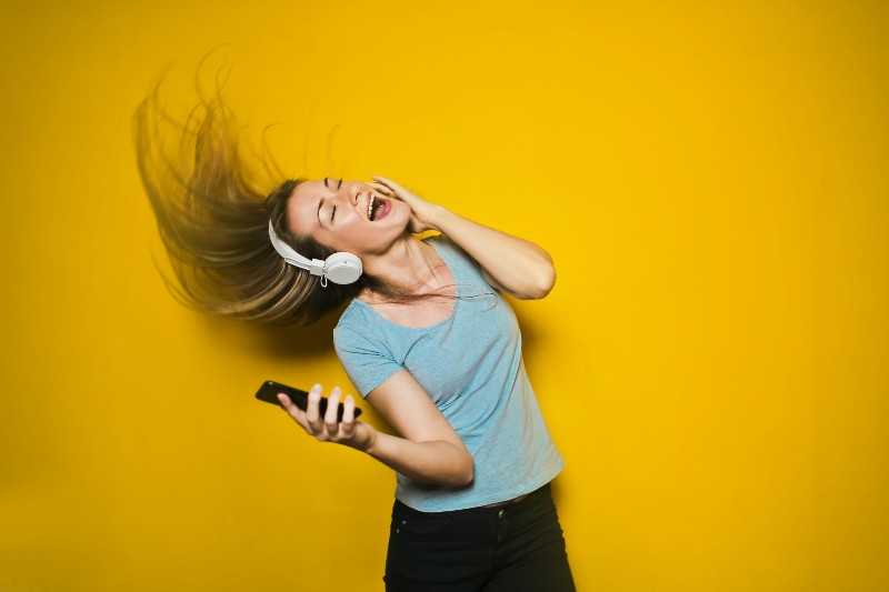 woman listening to music with yellow background