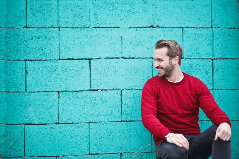 man smiling in front of blue brick wall