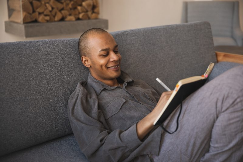 man reading book on couch smiling