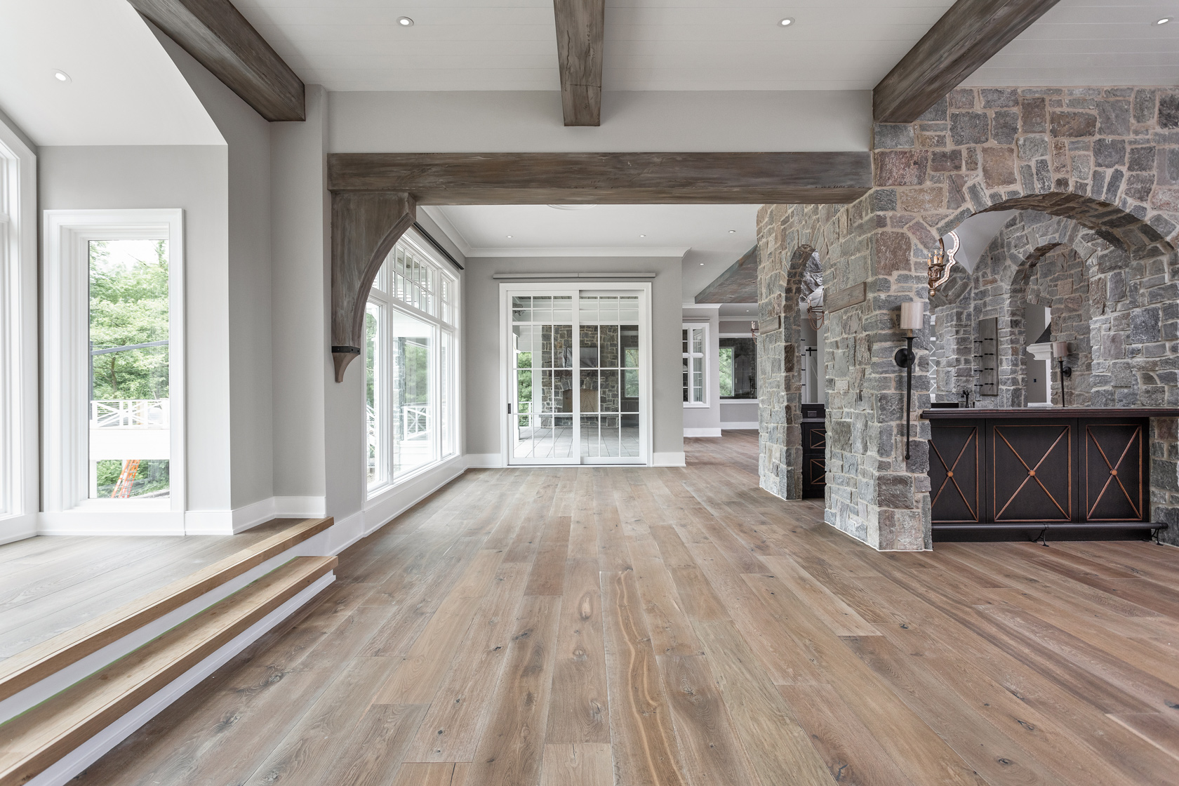 home interior with stone work, wooden floors, and natural sunlight