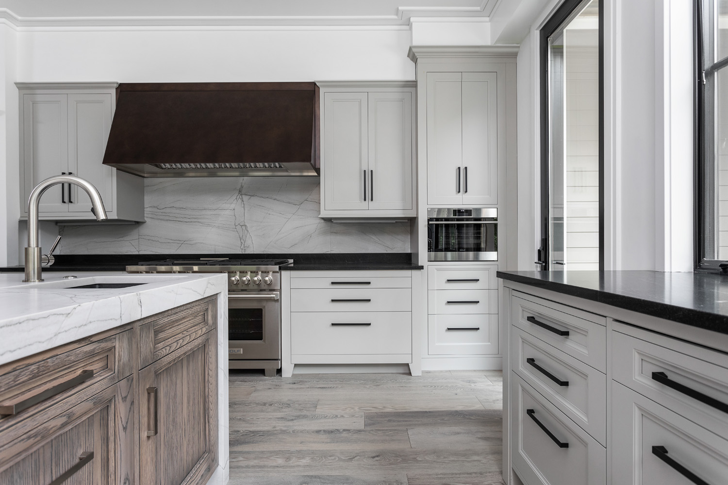 custom kitchen with wooden floors, stainless steel appliances, white cabinets, and dark countertops
