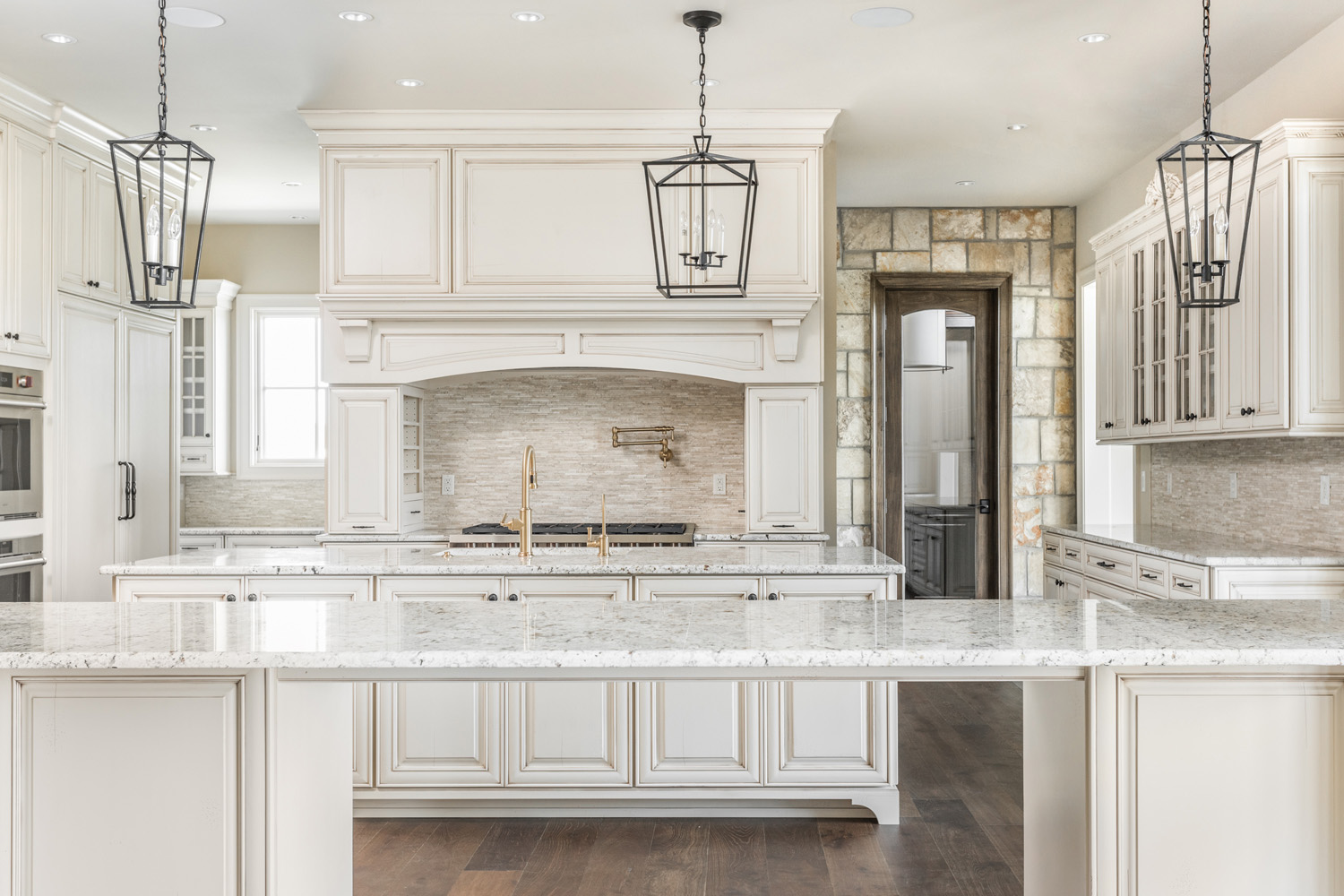 modern and traditional custom kitchen with stone countertops, wooden floors, white cabinetry, and pendant lighting