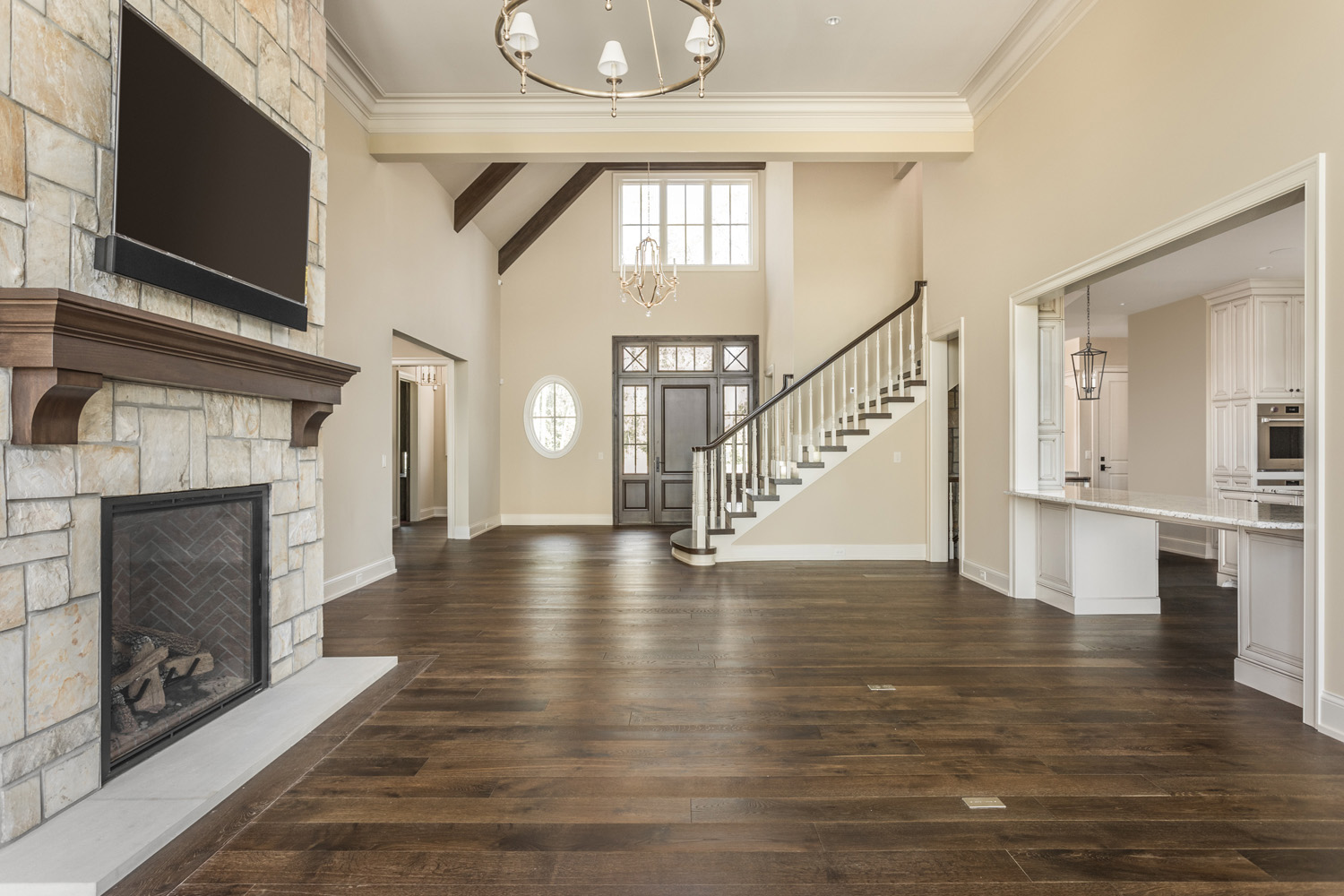 living room inside custom home with high ceilings, wooden floors, fireplace, and staircase