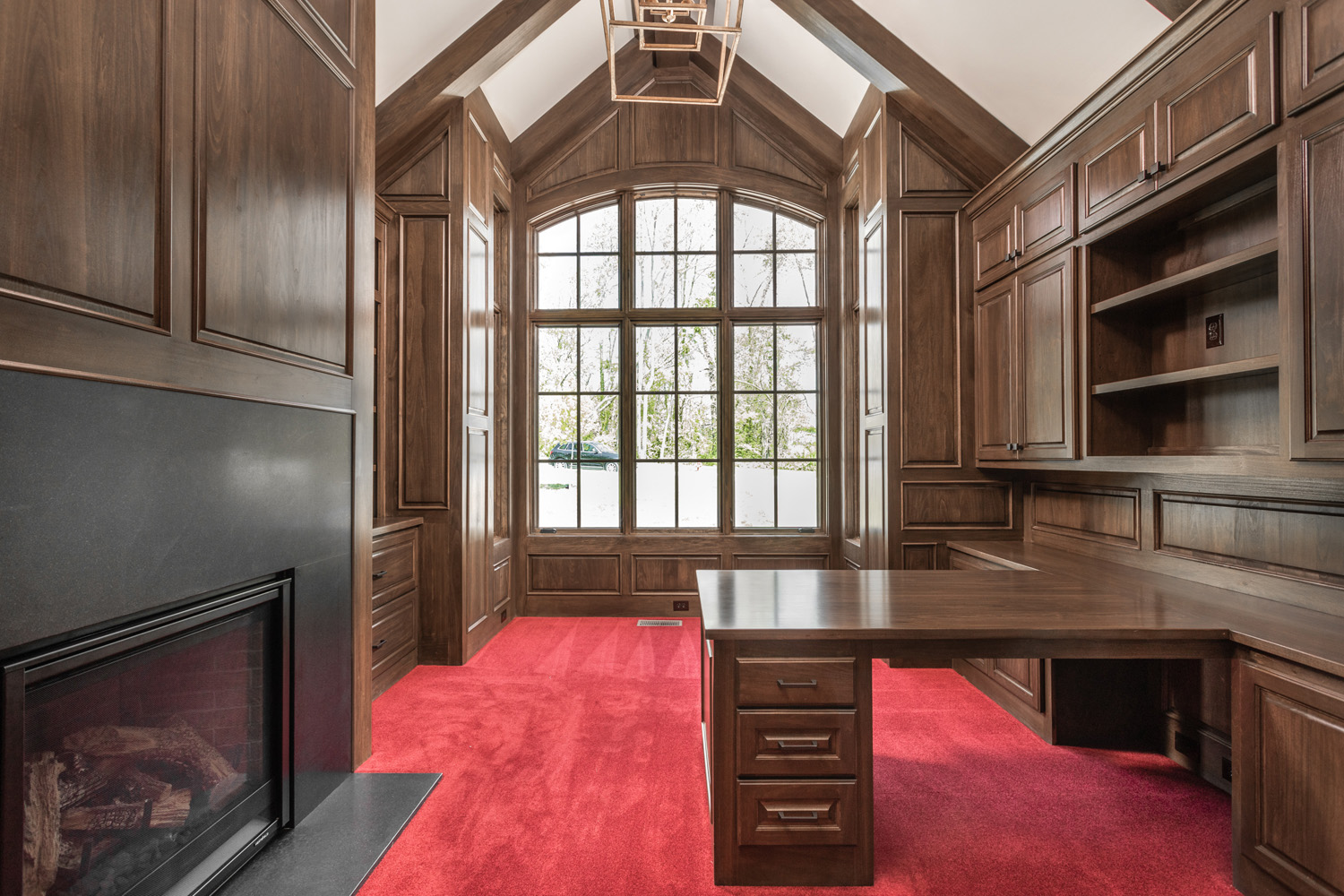 office inside custom home with red carpet, natural sunlight, desk, and carpentry work