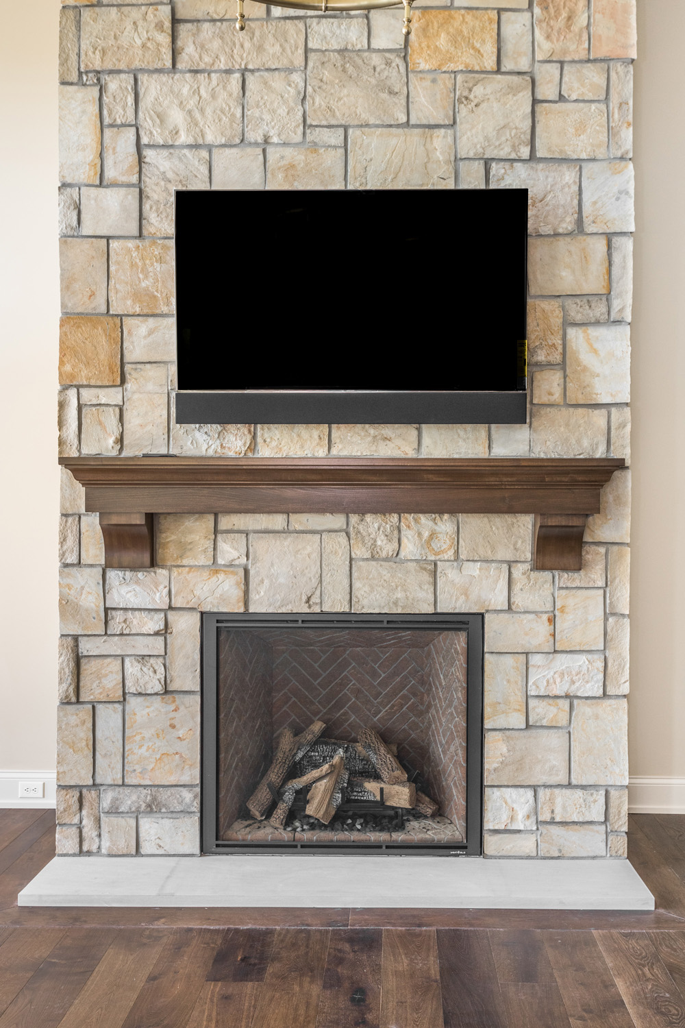 fireplace with stone work and hanging TV inside custom home