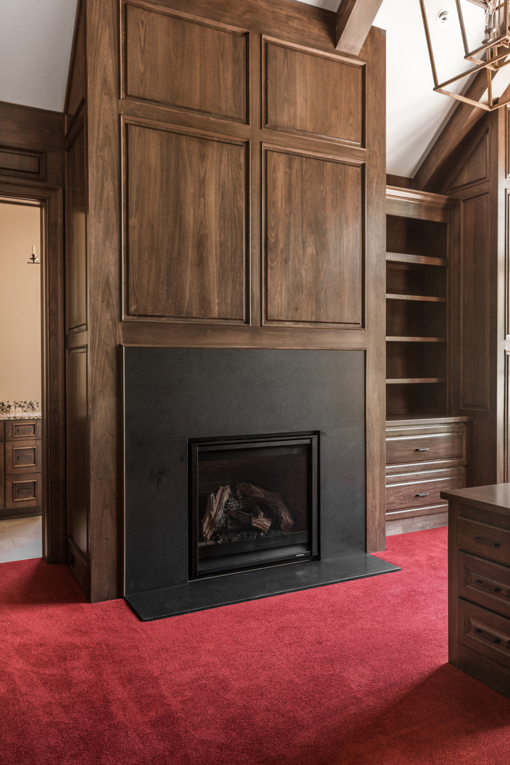 office fireplace inside custom home with red carpet and carpentry work