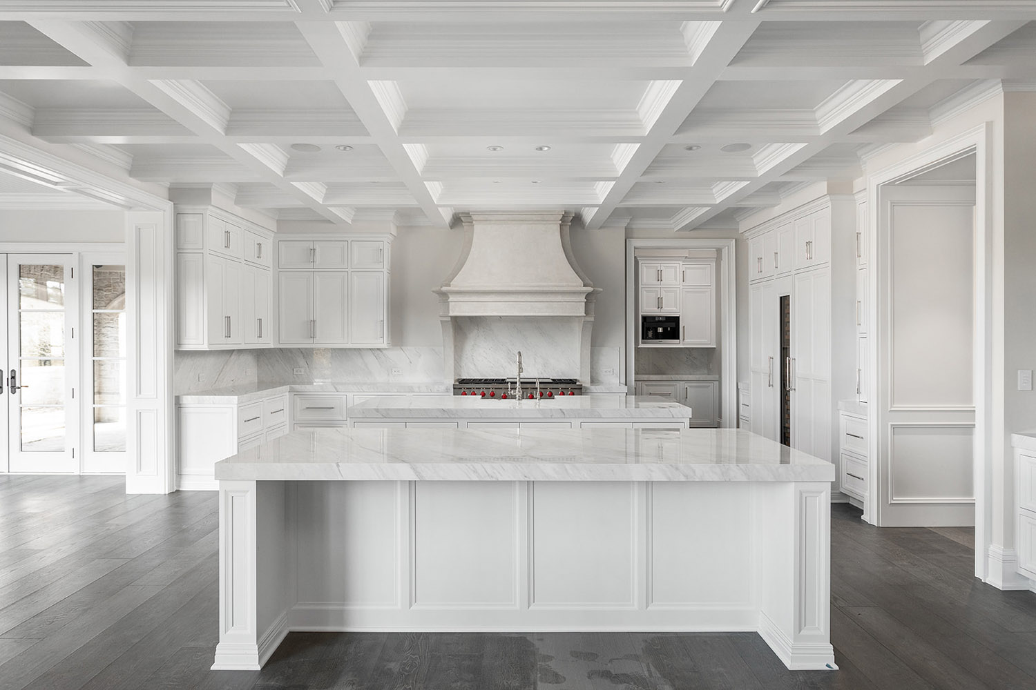 custom built kitchen with white cabinets and wood floors