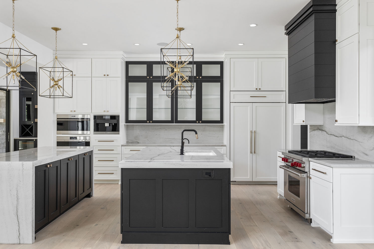 custom luxury home kitchen with wood floors, black cabinets, and marble backsplash