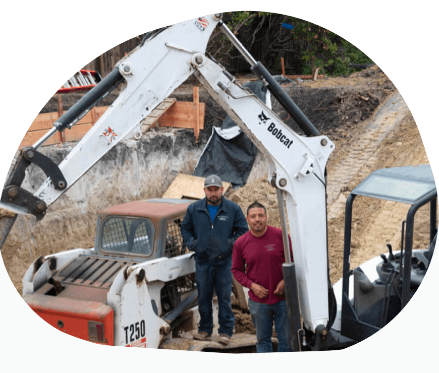 Owner Edgar Ochoa and his colleague standing next to an excavator in shape mask.