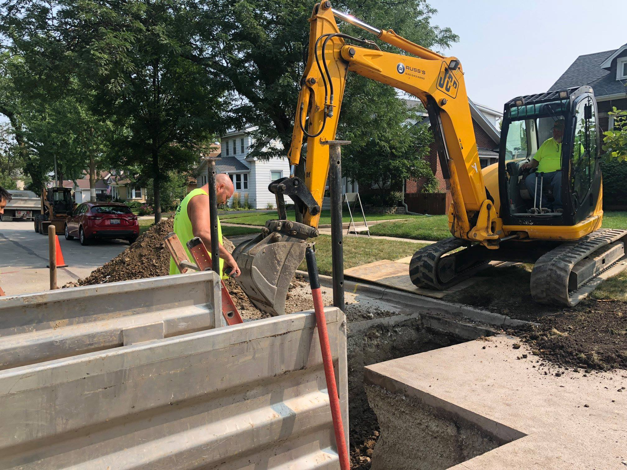 Addison plumbing job in residential street with excavator and Russ's team