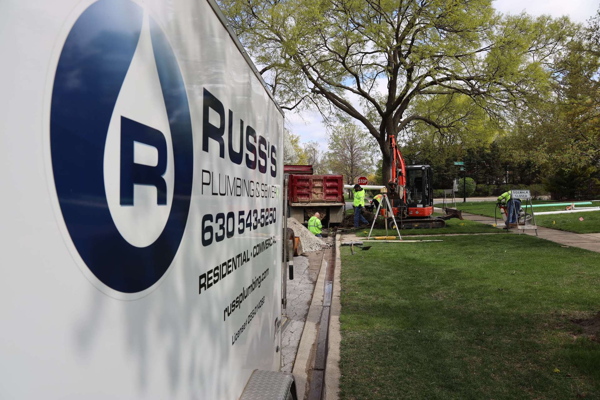 Russ's Plumbing & Sewer Inc. white truck in front of job site
