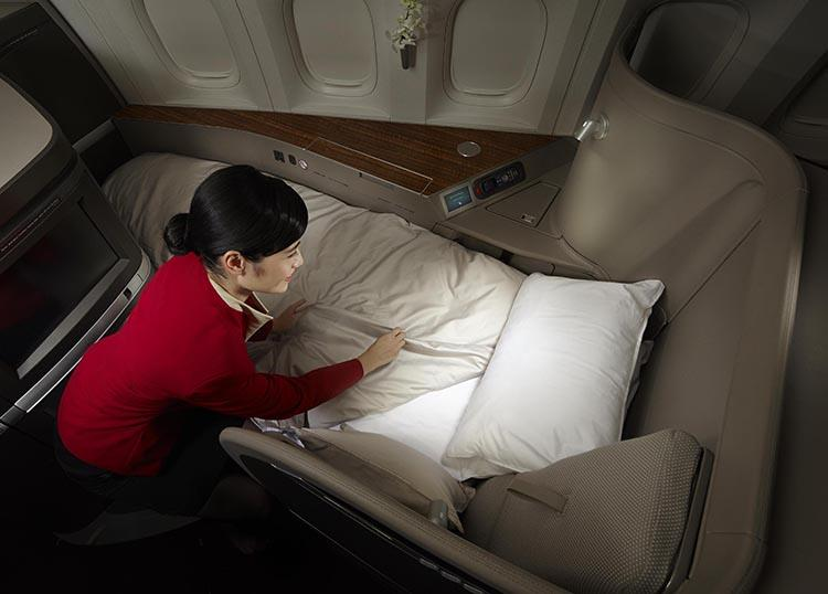 Cathay Pacific flight attendant making a bed in First Class
