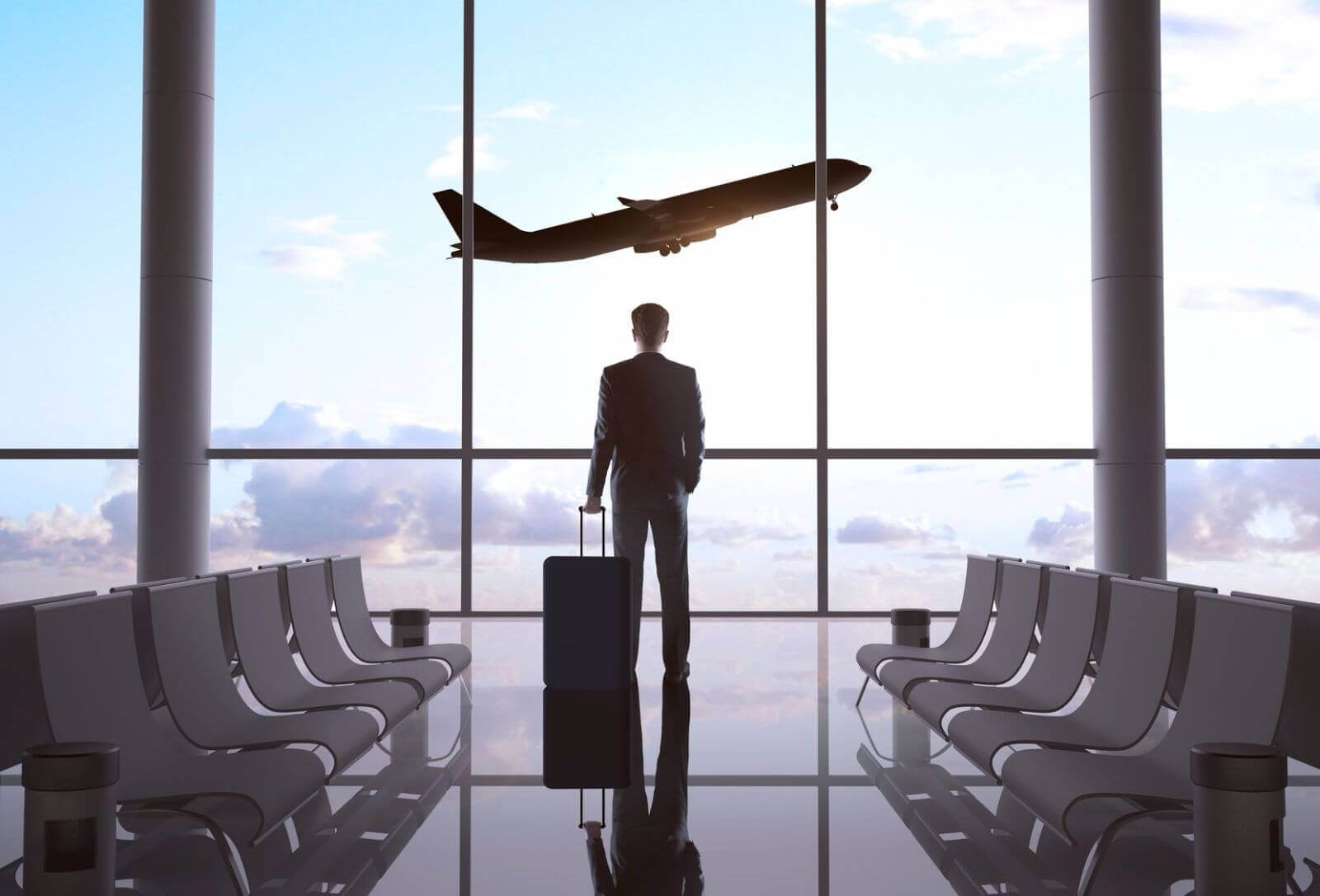 man watching an airplane take off from the airport terminal