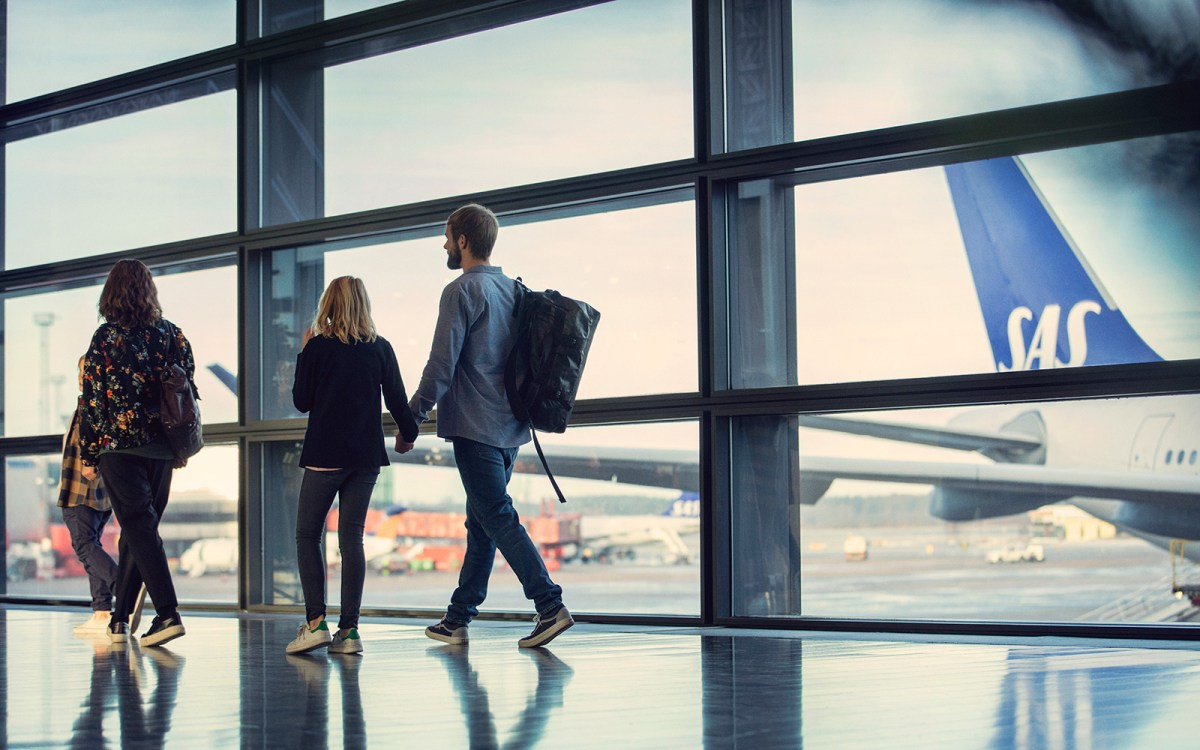 couple walking in airport terminal looking out window at airplane parked at the gate