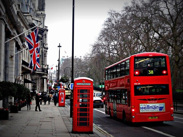 Double decker red bus and iconic telephone booth on the streets of London, England