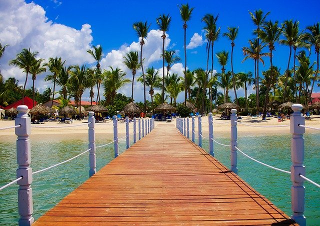 dock in Dominican Republic with palm trees, blue sky, and Caribbean water view.