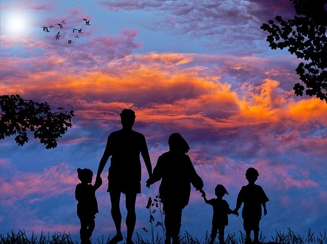 family of 5 staring into a beautiful sunset with clouds