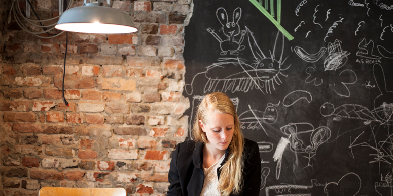 SPX Agency: The Student Hotel girl with wall and blackboard with drawings behind