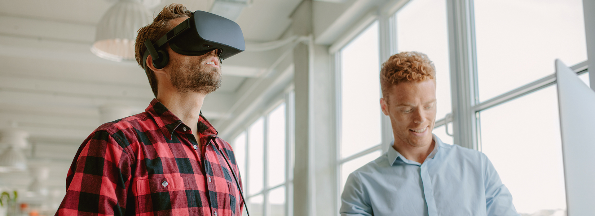 two guys trying virtual reality goggles
