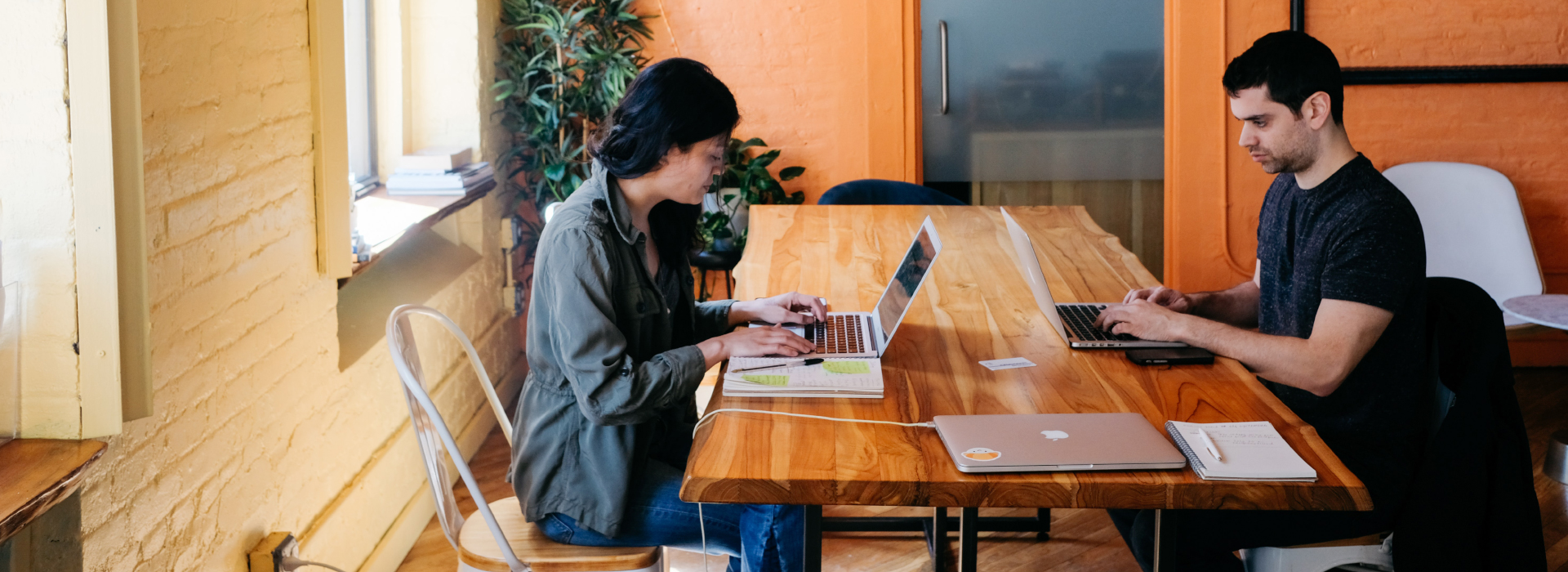 Couple working with laptops on wooden table