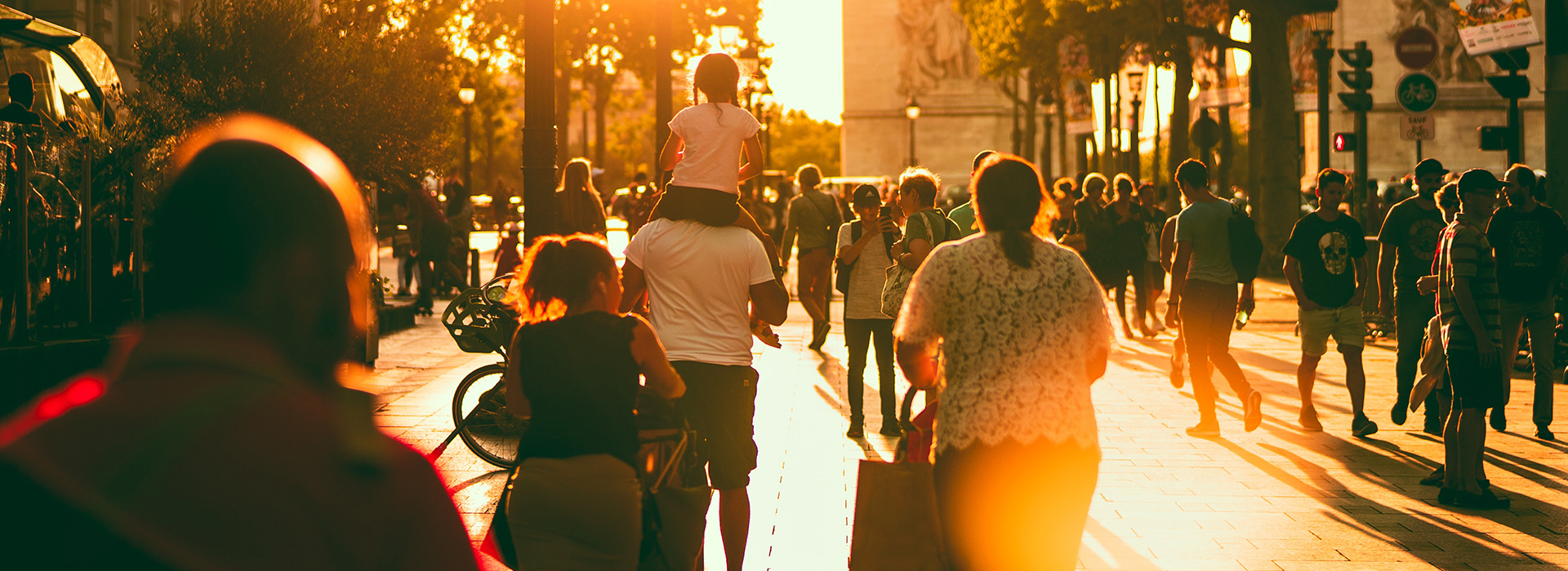 Groups of people walking on a street with the sunset