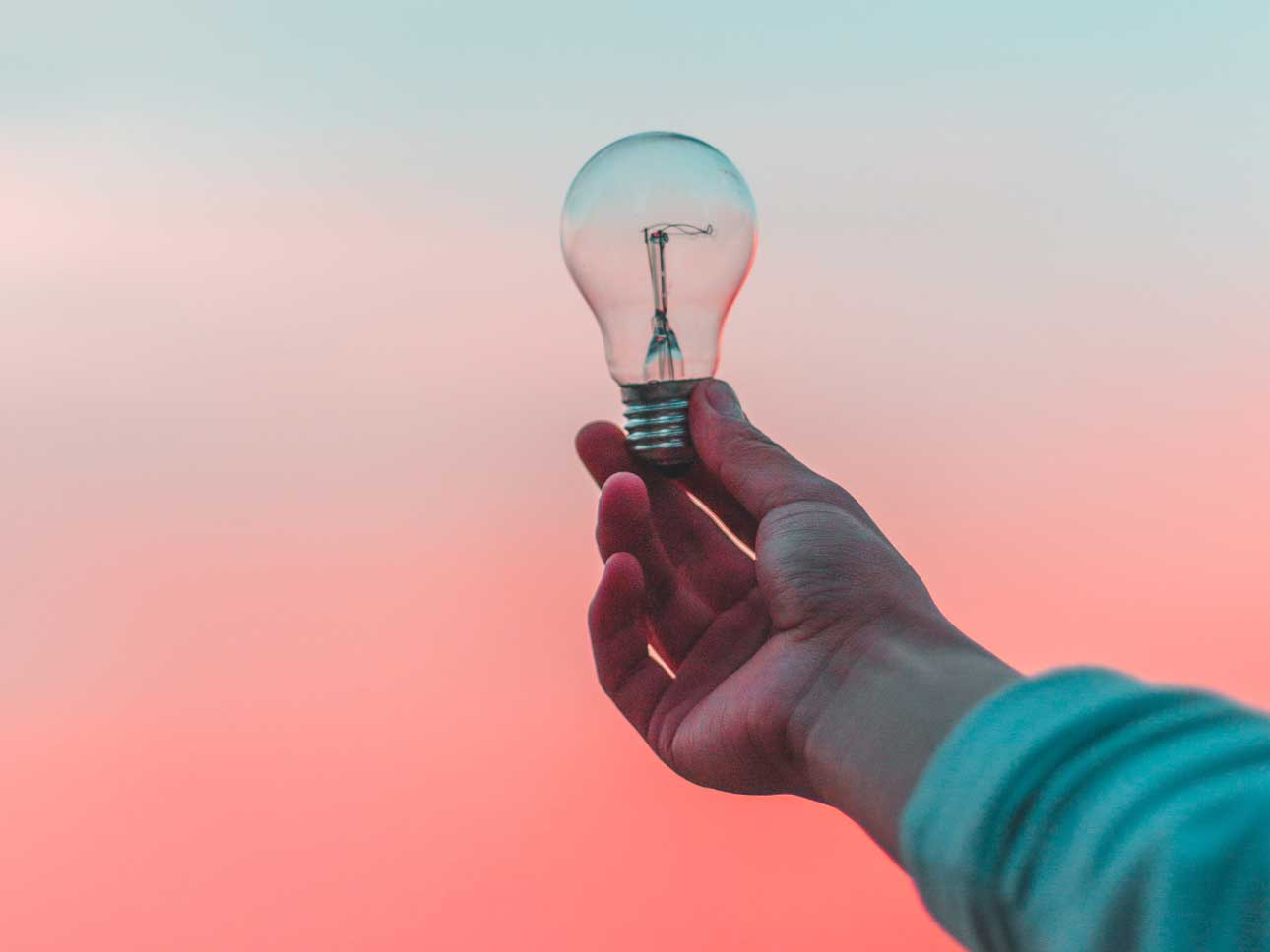 A hand holding a light bulb in front of a sunset.