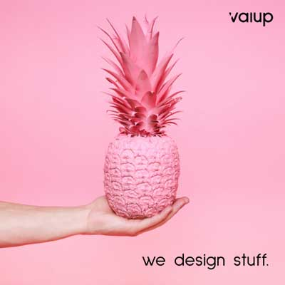 Hand holding pineapple on pink background.