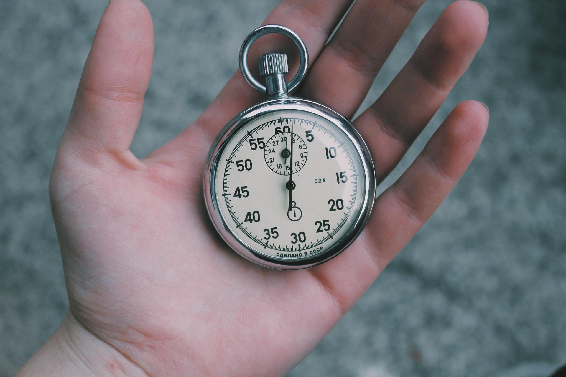 Eine Hand, die eine Taschenuhr hält.