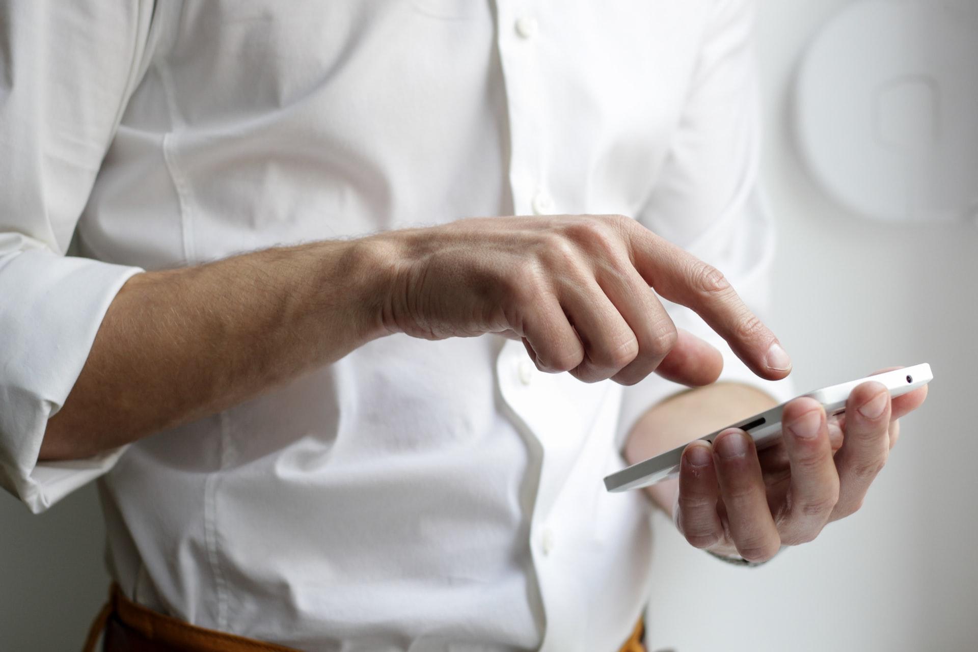 Ein Mann der ein Smartphone in der Hand hält.