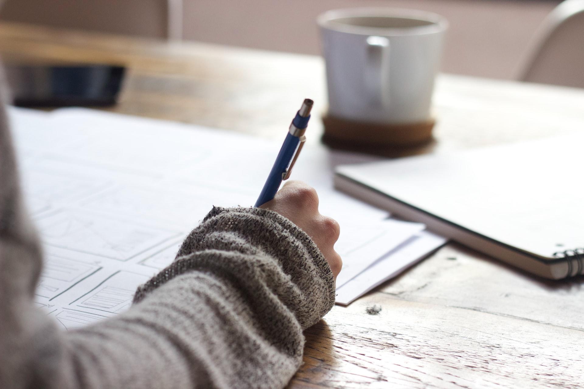 Eine Person sitzt an einem Tisch und schreibt auf Papier.