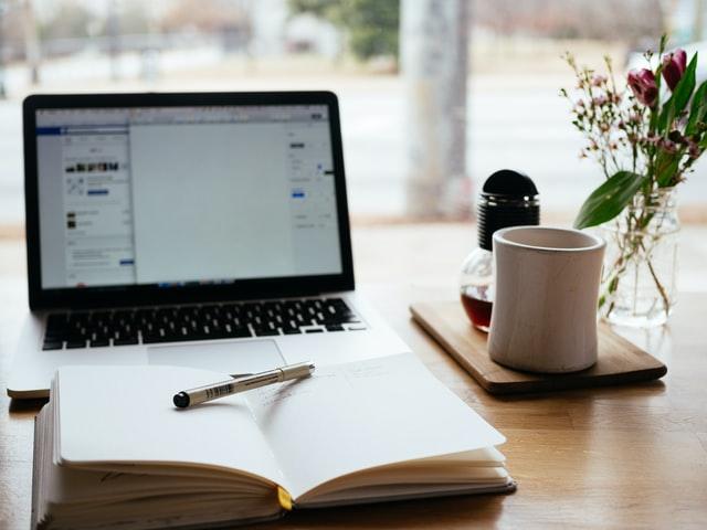 Ein Laptop und ein Buch mit einem Stift auf einem Tisch.