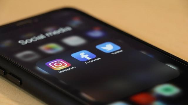 Ein Smartphone mit den App-Icons von Instagram, Facebook und Twitter.