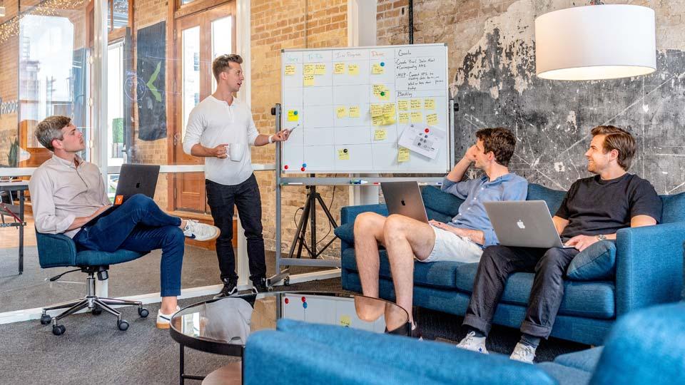 Vier Männer auf Sofas und Stühlen diskutierend vor einem Whiteboard.