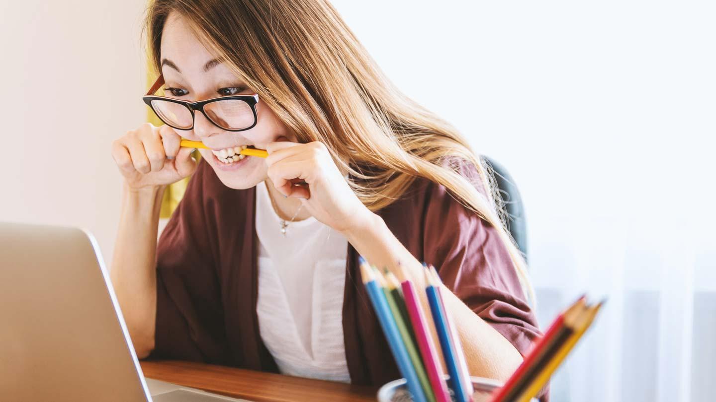 Eine gestresste Frau vor einem Laptop an einem Schreibtisch.