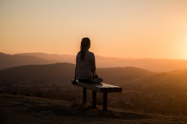 Eine Frau auf einer Bank vor einem Bergpanorama bei Sonnenuntergang.