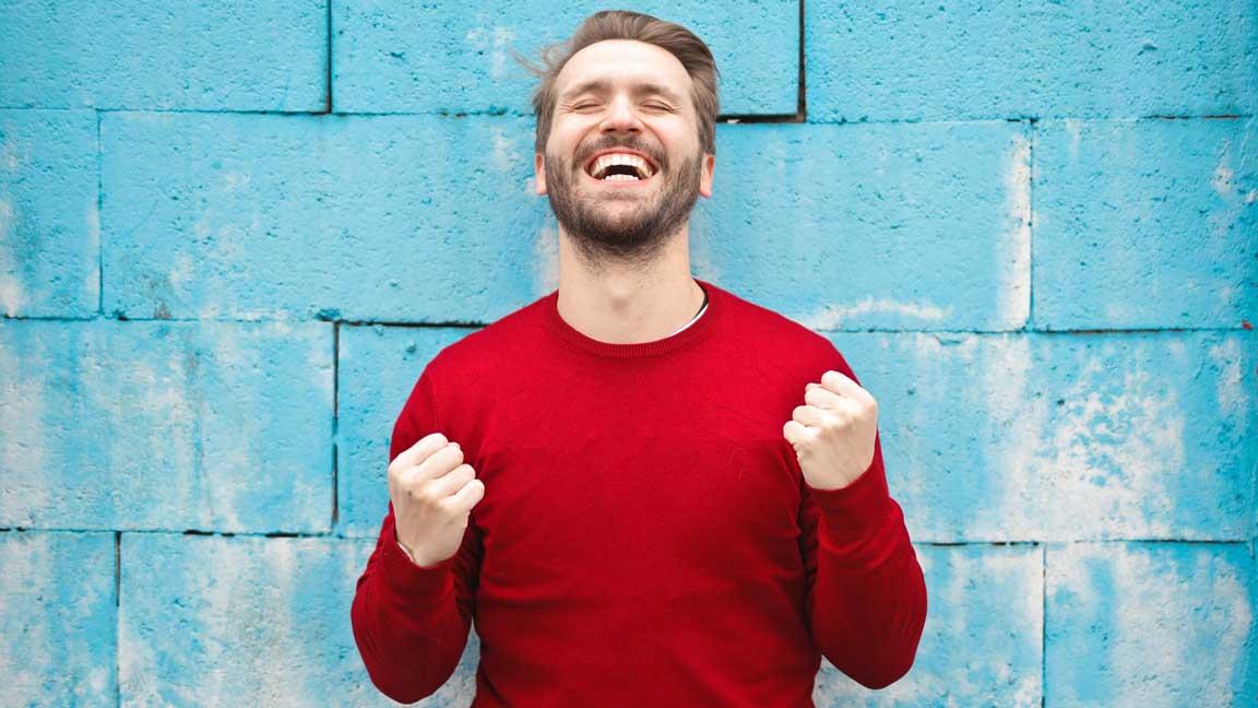 Ein sich freuender Mann vor einer blauen Wand.