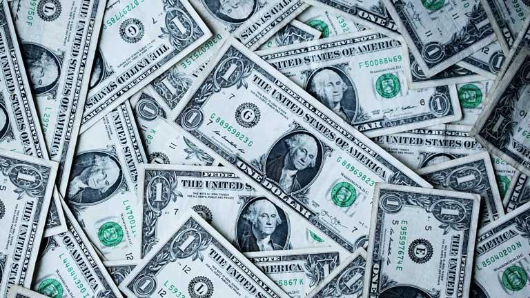 Dollar-Noten durcheinander auf einem Haufen von oben fotografiert.