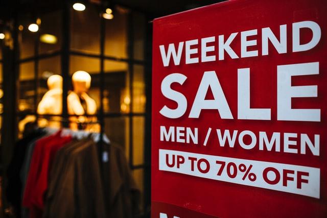 Ein Schild mit eine Sale-Ankündigung vor dem Hintergrund eines Klamottenladens.
