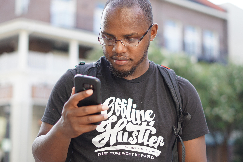 black man walking and looking at his phone