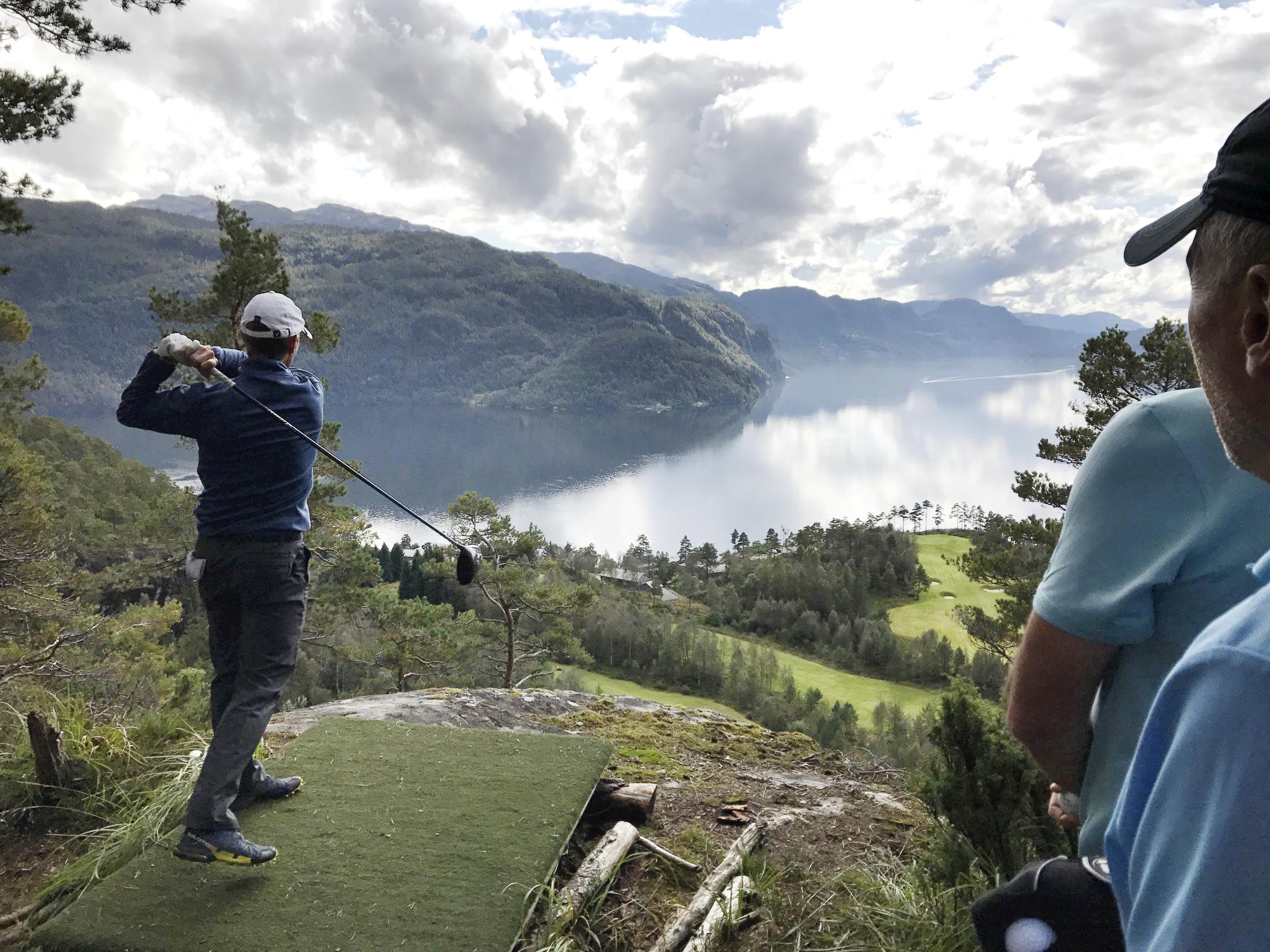 Golfspiller slår utslag under Eagle Nest Challenge 120 høydemeter over golfbane.