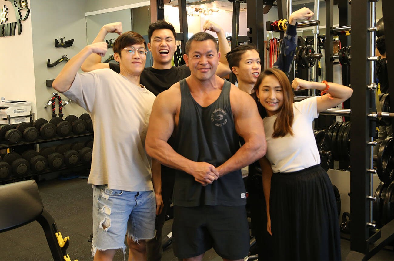 A group photo on set of our 4-person crew with Wallace Siu, all flexing and making various facial expressions.